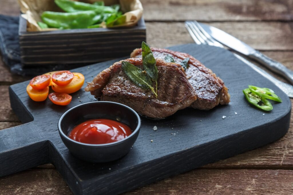 Meat Picanha steak, traditional Brazilian cut on black cutting board.